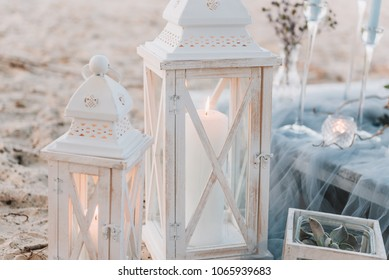 Big candles next to elegant table set up in blue pastels for a beach wedding