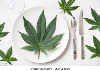 Big cannabis leaf on a dinner plate surrounded by more left overhead view
