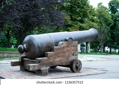 A big cannon placed outside a touristic attraction.