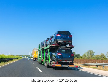 Big car carrier trailer with cars on bunk platform. Car transport truck on the highway. Space for text