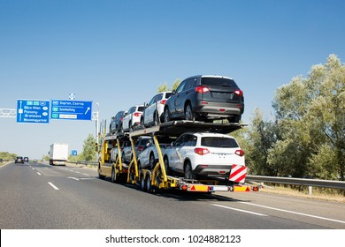 Big car carrier trailer with new cars for sale on bunk platform. Car transport truck on the highway
