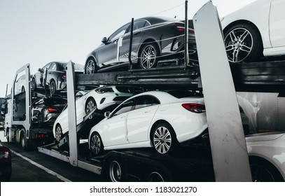Big car carrier truck of new luxury sport  german cars for batch delivery to dealership . Full load transport truck of new powerful new vehicles. Automotive industry  rent  shipping background.