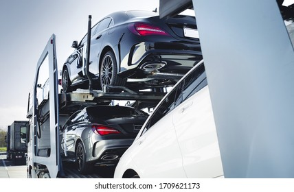 Big car carrier truck of new luxury sport german cars  delivery to dealership . truck of new powerful  new vehicles. Car detailing : Glass coating Automotive industry buy  rent  shipping background.