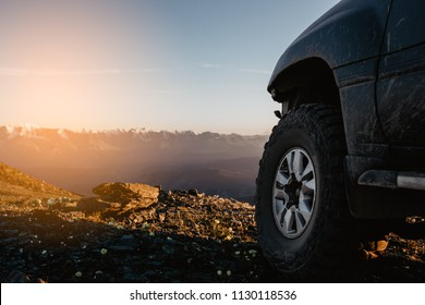 Big car wheel is standing on the rocks on mountain backdrop