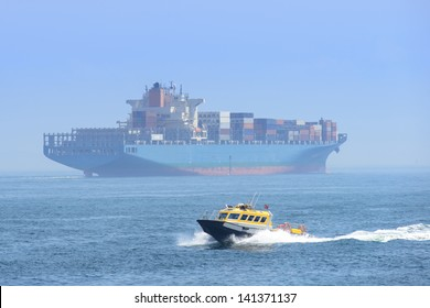 Big Cargo ship with fast small boat