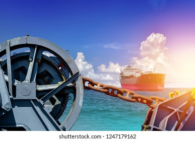 Big chain for Mooring winch, Mooring winch lass rope anchor at ship forward in shipyard of large with Big Chain and rusty with blue rope in drum and cargo ship sailing in the sea background.