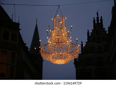big chandelier with a lot of led lights as Christmas decoration in front of the silhouettes of old traditional houses in the historic city of Bremen, Germany at dawn