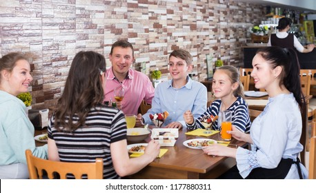 Big cheerful family having fun and dinning in cafe