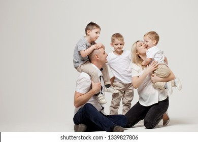 Big and cheerful family, mom dad and three sons. Happy together. family portrait on light grey background.