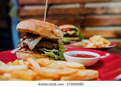 Big cheeseburger and chips on a plate. Restaurant
