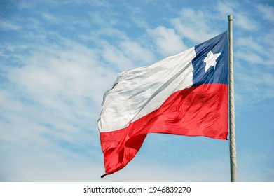 Big Chilean flag waving in front of blue sky with copy space. Chile country flag on a pole for identity and patriotism concept. Nation and state emblem, politics and union.