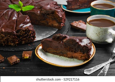 Big chocolate cake torte. Ingredients for chocolates cake torte mint, chocolate chips. Slices chocolate cake on saucer. Drink hot chocolate cocoa (coffee) in cups. Black wooden background.