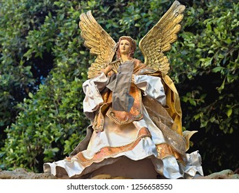 big Christmas angel with golden wings and lush robe in gold and beige. The angel has a harp in her hand is female with curly brown hair..