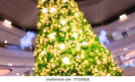 big christmas tree blurred background light with a lot of bokeh among the level of department