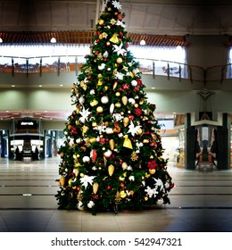 big christmas tree with colorful lights and christmas decorations in front of shop on street in