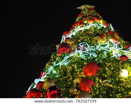 big christmas tree lighting from low angle view at night in christmas festival with black background