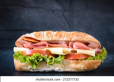 Big ciabatta sandwich with meat and cheese on dark background