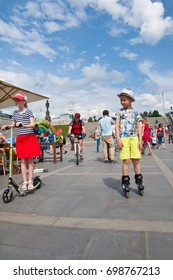 Big city picnic, Ekaterinburg, Russia, 06/20/2017, Girl in a red skirt and a vest on a scooter, a boy with a hat and yellow shorts on rollerskates.