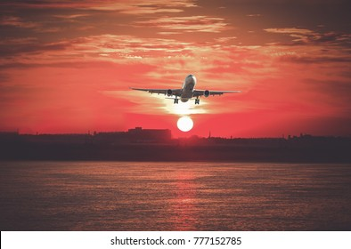 Big civil passenger plane flying up in sky at sunrise time