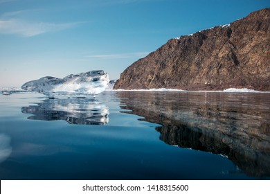 Big clean ice floe on the background of mountains and reflection on lake Baikal