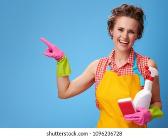Big cleaning time. happy modern woman in a yellow apron with kitchen sponge and a bottle of detergent pointing at something on blue background