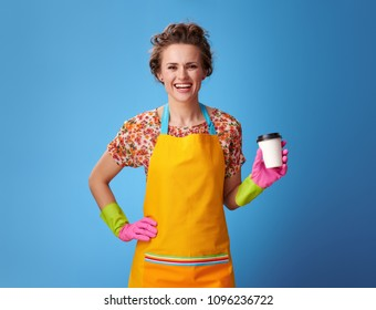 Big cleaning time. happy young housewife in a yellow apron with a coffee cup against blue background