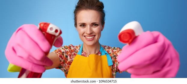 Big cleaning time. happy young housewife in a yellow apron using bottles of cleaning detergent as guns isolated on blue