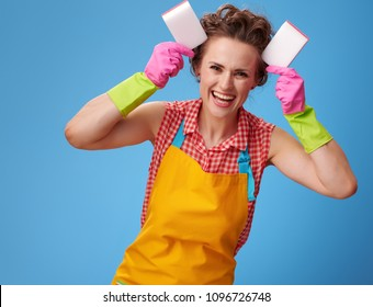 Big cleaning time. happy young housewife with rubber gloves making ears with kitchen sponges isolated on blue