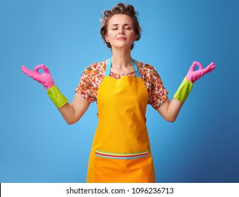 Big cleaning time. relaxed young housewife in a yellow apron doing yoga isolated on blue