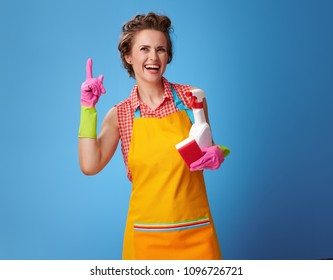 Big cleaning time. smiling modern housewife with rubber gloves and kitchen sponge and a bottle of detergent got idea against blue background