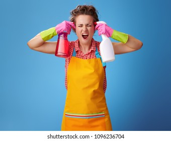 Big cleaning time. stressed modern housewife with rubber gloves wanting to shoot herself from a bottles of detergent isolated on blue background