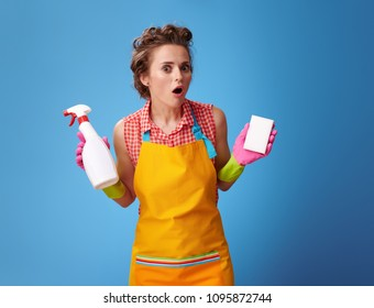 Big cleaning time. surprised young woman in a yellow apron with kitchen sponge and a bottle of detergent against blue background