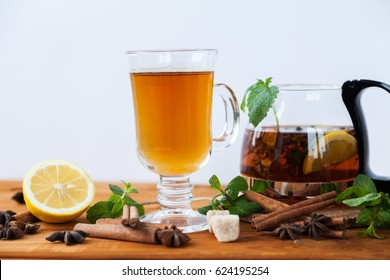 Big clear glass and teapot of hot black herbal tea with lemon, mint and Melissa leaves on light rustic wooden table. Summer, Autumn, winter drink. Cinnamon and cane sugar for decoration.