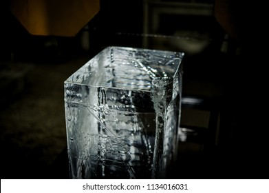 Big clear ice cube standing on the floor on the ice production plant under the light equipment on the blurred background
