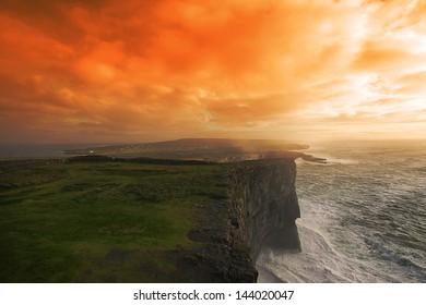 big cliffs on Atlantic ocean at sunset.Aran Islands.Ireland.orange filter added