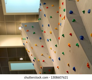 Big climbing wall inside. Indoor climbing wall. Sporty background with colorful climbing grip.