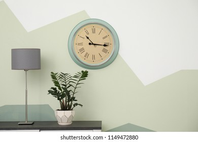 Big clock hanging on color wall. Time concept