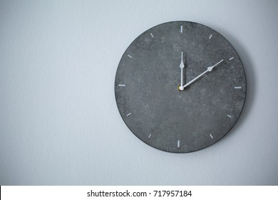 Big clock hanging on grey wall