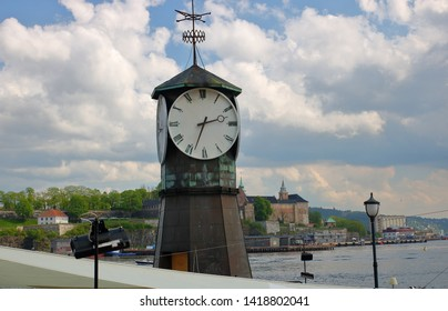 Big clock in Oslo city cen, opposite shore with fortress on hillter, Norway, Baltic sea bay