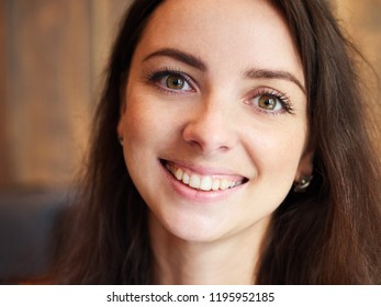 Big close up portrait of beautiful cute brunette girl in the cozy cafe near the window with shy smiling