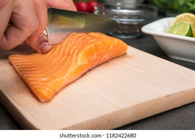 Big closeup on male hand with knife cutting steak from salmon fish on wooden cutting board with fresh food ingredients behind.