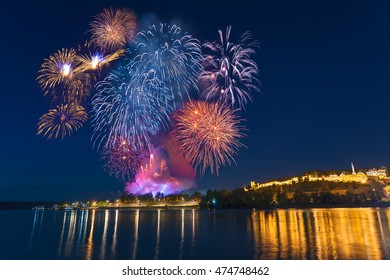 Big, colorful multiple fireworks at the foot of the famous tourist landmark Kalemegdan fortress at night, with reflection on river Sava, Belgrade - Serbia.