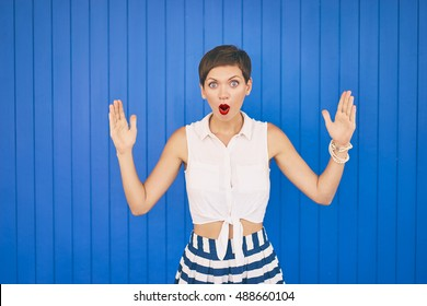 It is so big. Colorful studio portrait of pretty young woman showing big size with her hands. Blue background.