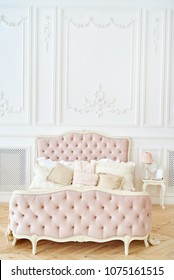 Big comfortable royal bed with pillows in elegant bedroom interior, copy space. Honeymoon suite, free space. Female bedroom in pink and white colors. Luxury bed in romantic style. Boudoir