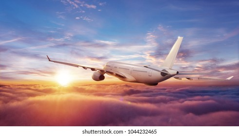 Big commercial airplane flying above clouds in sunset light. Travel and business theme.