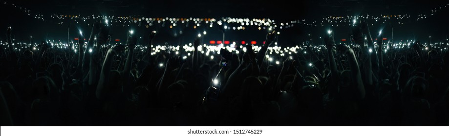 Big concert crowd background.Silhouette of many young people with smartphones lights in hands having fun on popular musical event in huge music hall.Festival audience wave hands to famous rock singer