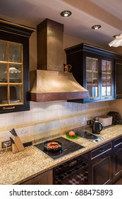 Big copper range hood, cooktop in the black kitchen interior