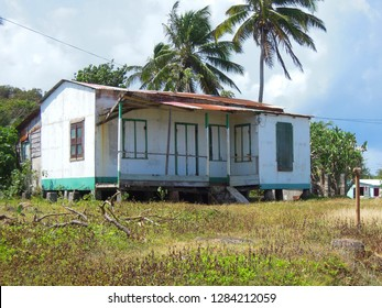 Big Corn Island Nicaragua Central America typical house architecture on cinder blocks with coconut palm trees blue sky