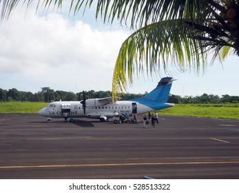 BIG CORN ISLAND, NICARAGUA-AUG. 27: Tourists disembarking from twin prop plane on tarmac airport of Big Corn Island, Nicaragua, Central America on August 27, 2016.