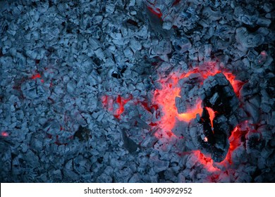 Big cracked piece of smoldering firewood log with red flame inside and gray ashes background. Burnt campfire texture closeup. Natural burning wooden coal surface.